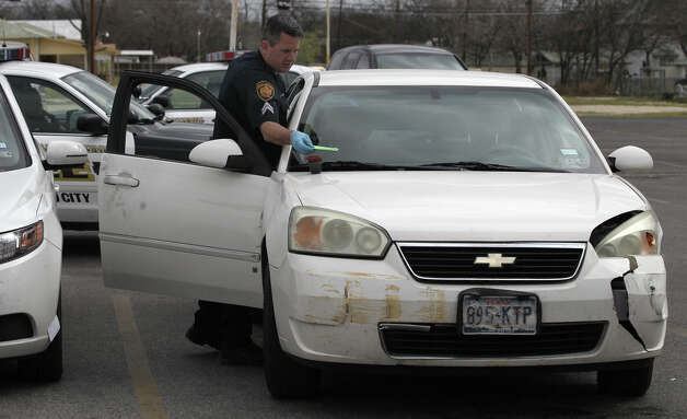 A San Antonio police officer gathers evidence Monday February 4, 2013 from a car found abandoned in the parking lot of the Little Red Barn steakhouse on south Hackberry street. Police believe the vehicle was stolen and was involved in several East Side crashes including one on North Monumental street that pushed a Jeep into the front of a house. Police are searching for the male suspect. Photo: JOHN DAVENPORT, San Antonio Express-News / ©San Antonio Express-News/Photo Can Be Sold to the Public