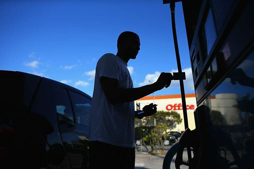A customer pays for gas in Miami, where, as in the rest of the country, pump prices are much higher