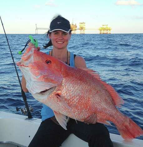 Tracy Allred holds a 38.25-inch red snapper she caught about 80 miles off Sabine Pass in January.  The fish, which may have topped  the current Texas red snapper record of 38.13 pounds, was released because red snapper season is closed in Gulf water under federal control. Photo courtesy of Travis Allred Photo: Picasa