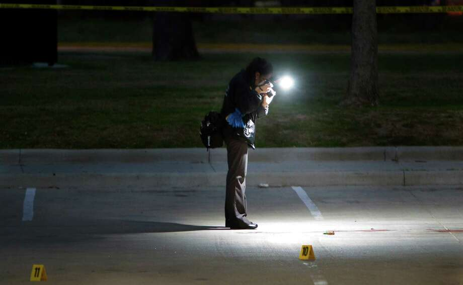 Police investigate a homicide at T.C. Jester Park on Monday. Houston police said a woman was hit and killed by a vehicle in the parking lot about 3 a.m. Police are seeking a man believed to be her husband or boyfriend. Photo: Cody Duty, Staff / © 2013 Houston Chronicle