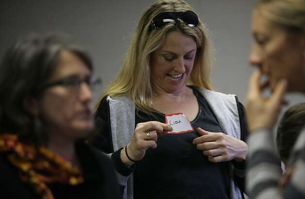 Firefighter Lisa Holdcroft (middle) putting on a name tag while attending the San Francisco  Firefighters Cancer Prevention foundation giving an informational  meeting for female firefighters at fire station #7 in San Francisco, Calif.,  on Friday, January 25, 2013.  She is flanked by Rachel Morello-Frosch (left) from UC-Berkeley's school of public health and firefighter Lt. Heather Buren (right) #5.  Firefighter Lisa Holdcroft has breast cancer. Photo: Liz Hafalia, The Chronicle