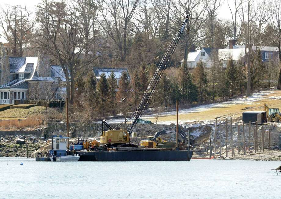 An excavator is still stuck  in the water in Greenwich Harbor in Greenwich, Monday,  Feb, 4, 2013.An excavator that got stuck in sand Friday morning while doing work on a breakwater at a Belle Haven residence is slated to be towed away Tuesday morning. The excavator is partially obscured by a crane that was brought in Monday to help prevent the excavator from falling over, a state environment official said. The property at 110 Field Point Circle, the former home of the late comedian Victor Borge. State environment officials will be investigating to see if the Rhode Island-based contractor followed the certificate of permission granted last March in order to work on the breakwater and the jetty. A boom had been placed around the excavator Friday by environment officials but no evidence of any fuel spill has been found, said an environment department spokesman. Photo: Helen Neafsey / Greenwich Time