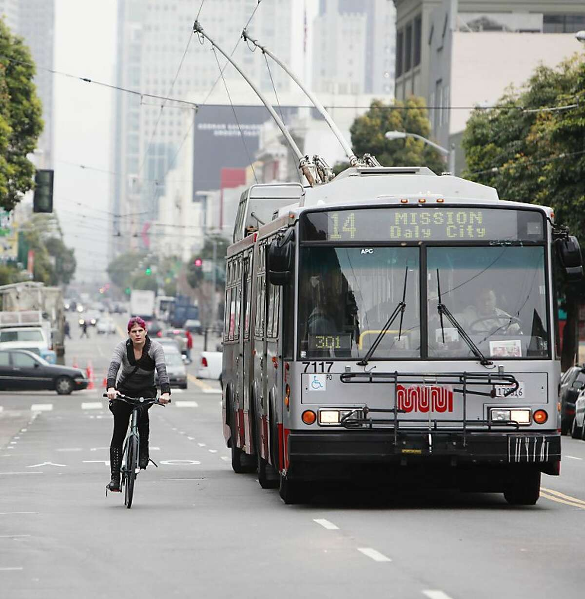 Naomi Seyfer of Berkeley on a bicycle and a 14 Mission line Muni bus make their way west bound on Mission Street on Monday, February 4, 2013 in San Francisco, Calif.