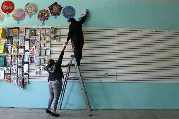 Sandra Rodriguez (left) and her niece Maritza Arreguin arrange merchandise in Rodriguez's storefront business in Hayward, Calif. on Wednesday, Jan. 30, 2013. Rodriguez is opening the party rental shop with the help of a microcredit loan from Grameen Bank.