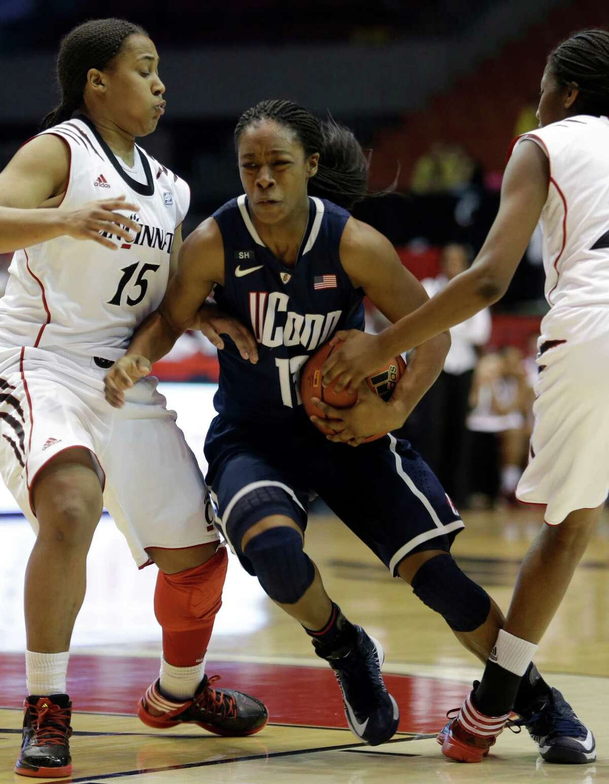 Connecticut guard Brianna Banks, center, drives between Cincinnati guard Alexis Durley (15) and guard Jasmine Whitfield, right, in the second half of an NCAA college basketball game on Saturday, Jan. 26, 2013, in Cincinnati. Connecticut won 67-31. (AP Photo/Al Behrman)