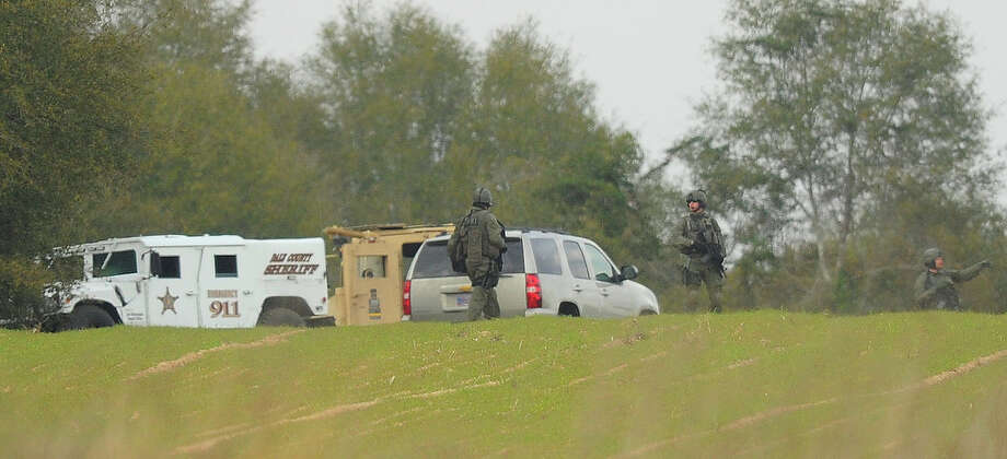 Armed law enforcement personnel station themselves near the property of Jimmy Lee Sykes, Monday, Feb. 4, 2013 in Midland City, Ala. Officials say they stormed a bunker in Alabama to rescue a 5-year-old child being held hostage there after Sykes, his abductor, was seen with a gun. (AP Photo/AL.com, Joe Songer) Photo: Joe Songer, MBI / AL.com
