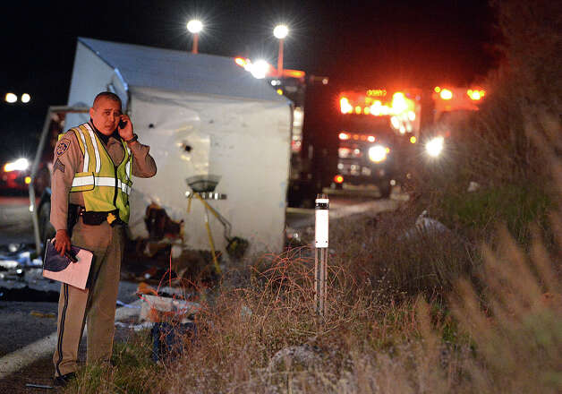 A California Highway Patrol officer stands near the crash scene where at least eight people were killed and nearly two dozen were injured when a bus carrying a group from Tijuana, Mexico crashed with two other vehicles on its way back from Big Bear Lake on Highway 38 north of Yucaipa, Calif., Sunday, Feb. 3, 2013. Both sides of the highway remained closed two and a half hours after the crash and it was unclear when it would reopen. (AP Photo/The Sun, Rick Sforza) MANDATORY CREDIT Photo: Rick Sforza