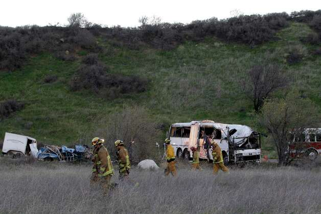 San Bernardino Fire Department  Investigators search through the brush Monday Feb. 4, 2013, at the scene of a tour bus accident that killed at least 8 Sunday evening in the mountains near San Bernardino, Calif.  ( AP Photo/Nick Ut) Photo: Nick Ut