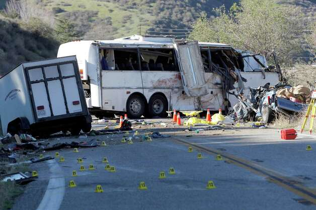Evidence markers dot the road in front of the wreckage of a tour bus in the Southern California mountains near San Bernardino Monday Feb. 4, 2013.  The tour bus carrying dozens of men, women and children from Tijuana, Mexico, crashed killing at least eight people, authorities said. ( AP Photo/Nick Ut) Photo: Nick Ut