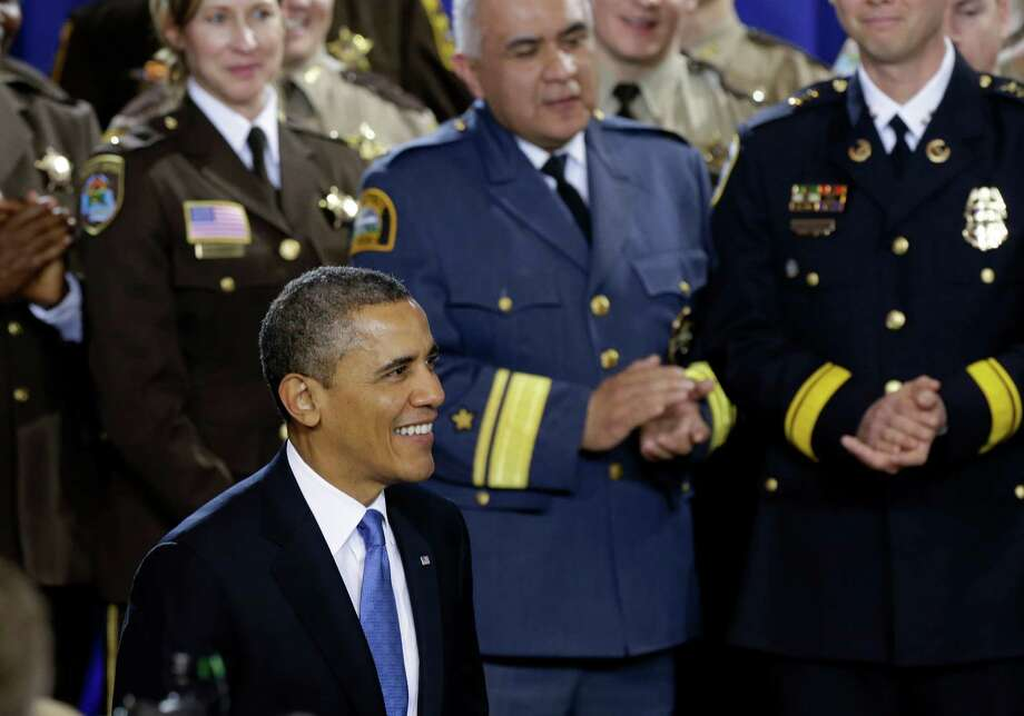 President Barack Obama is applauded prior to speaking about his gun violence proposals, Monday, Feb. 4, 2013, at the Minneapolis Police Department's Special Operations Center in Minneapolis, where he outlined his plan before law enforcement personnel.  (AP Photo/Jim Mone) Photo: Jim Mone, STF / AP