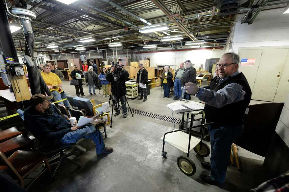 Auctioneer Scott Perry, right, of Batavia works the crowd for bids on state surplus office items Monday morning, Feb. 4, 2013, at Building 18 on the Harriman Campus in Albany, N.Y. (Skip Dickstein/Times Union) Photo: SKIP DICKSTEIN / 00021024A