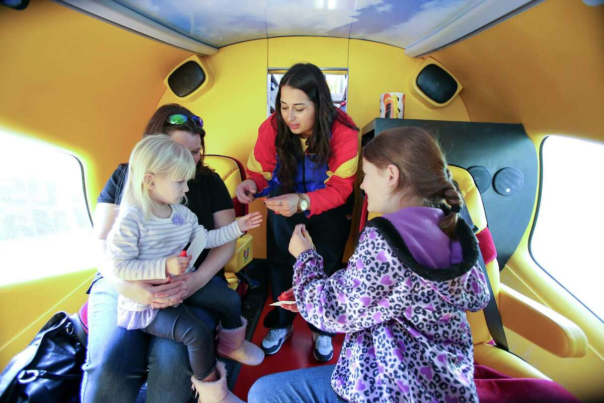 Emma Cuellar hands Oscar Mayer key chains, stickers and whistles to Robbie Durham and her daughters, Maggie, 3, and Kaitlynn, 10, inside the Wienermobile during a stop last week in Houston. The Durhams drove from Porter to see it.