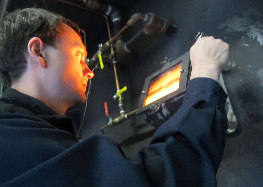 n this photo taken Jan 23, 2013, Brandon Smith, the brewing operations and engineering manager, checks on the boiler at the Alaskan Brewing Co. in Juneau, Alaska. The brewery has installed a unique boiler system that burns the company's dried, spent grain or waste accumulated by the brewing process into steam which powers the majority of the plant's operations. (AP Photo/Mark Thiessen) Photo: Mark Thiessen