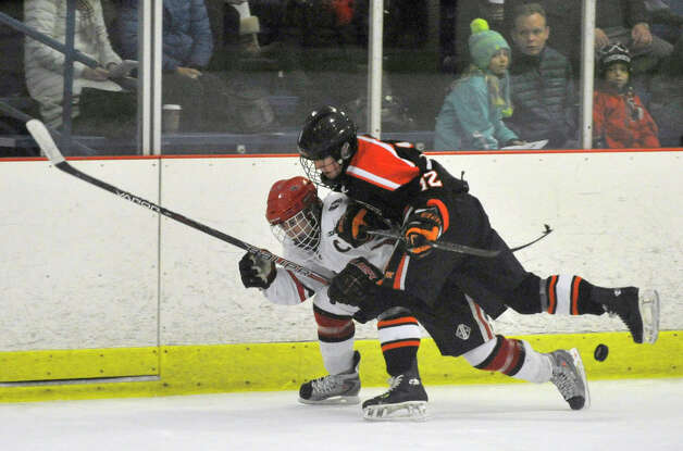 Ridgefield's James Kelly slams into Harry Stanton, of New Canaan, during their game at Darien Ice Rink on Monday, Feb. 4, 2013. New Canaan beat Ridgefield, 4-1. Photo: Jason Rearick / The News-Times