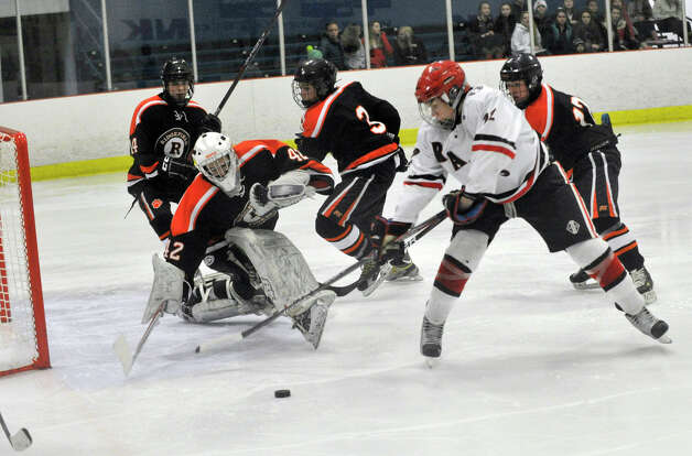 New Canaan's Patrick Hompe shoots on Ridgefield goalie Dustin Rausa during their game at Darien Ice Rink on Monday, Feb. 4, 2013. New Canaan beat Ridgefield, 4-1. Photo: Jason Rearick / The News-Times