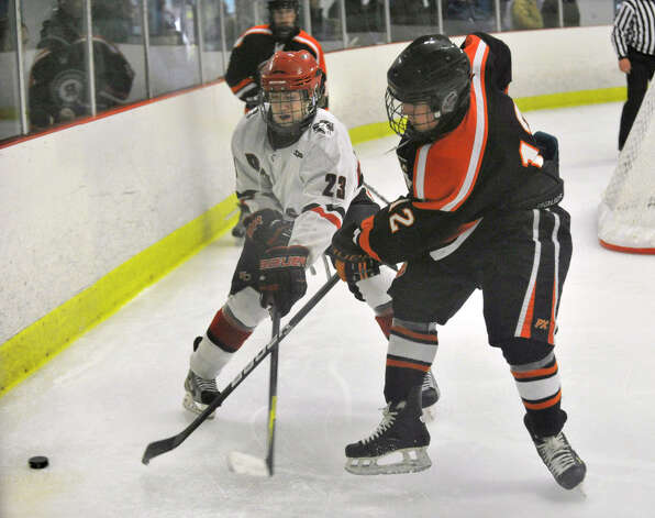 New Canaan's Luke Amero battles Ridgefield's James Kelly for control of the puck during their game at Darien Ice Rink on Monday, Feb. 4, 2013. New Canaan beat Ridgefield, 4-1. Photo: Jason Rearick / The News-Times