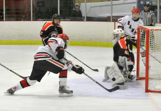 New Canaan's Davis Bruch shoots on Ridgefield goalie Dustin Rausa during their game at Darien Ice Rink on Monday, Feb. 4, 2013. New Canaan beat Ridgefield, 4-1. Photo: Jason Rearick / The News-Times