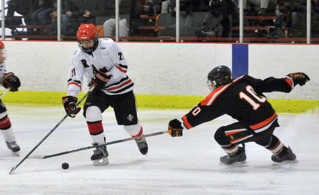 New Canaan's Parker Lewis evades Ridgefield's Shane Luery during their game at Darien Ice Rink on Monday, Feb. 4, 2013. New Canaan beat Ridgefield, 4-1. Photo: Jason Rearick / The News-Times
