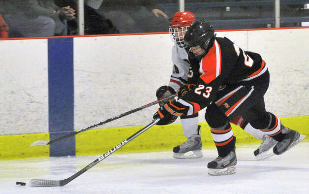 New Canaan's Harry Stanton battles Ridgefield's Ian Ball for control of the puck during their game at Darien Ice Rink on Monday, Feb. 4, 2013. New Canaan beat Ridgefield, 4-1. Photo: Jason Rearick / The News-Times