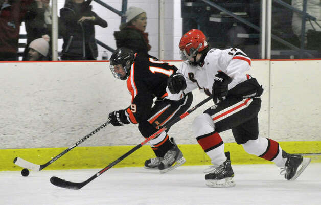 Ridgefield's Paul Garlick keeps the puck away fom New Canaan's Stephen Mettler during their game at Darien Ice Rink on Monday, Feb. 4, 2013. New Canaan beat Ridgefield, 4-1. Photo: Jason Rearick / The News-Times