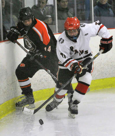 New Canaan's Parker Lewis keeps the puck from Ridgefield's Callan McCormick during their game at Darien Ice Rink on Monday, Feb. 4, 2013. New Canaan beat Ridgefield, 4-1. Photo: Jason Rearick / The News-Times