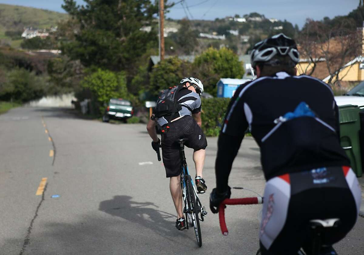 Brad Waldron checks on Bobby McMullen during a bike ride on January 24, 2013 in Mill Valley, Calif. McMullen's friends act as guides by shouting descriptions of turns and aberrations on the road to the blind McMullen when they go on bike rides. McMullen is an avid and accomplished skier, mountain biker, and road cyclist.