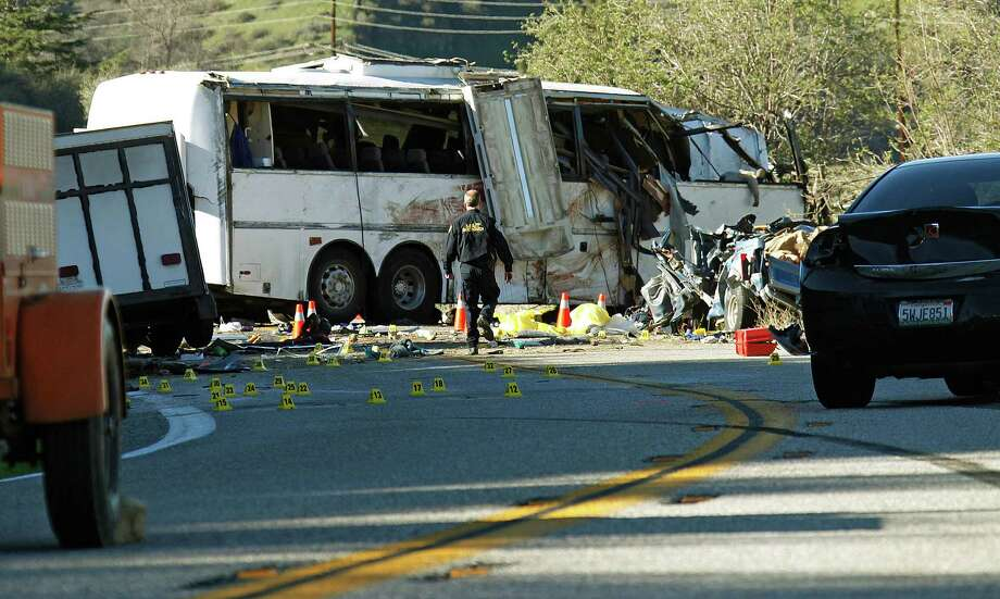 """A California Highway Patrol investigator gathers evidence Monday from the wreckage of a tour bus that crashed Sunday just north of Yucaipa, Calif., killing seven people.  The bus was carrying a tour group from Tijuana, Mexico.  """"When the bus spun, everything flew even the people,"""" one passenger said. Photo: Reed Saxon, STF / AP"""