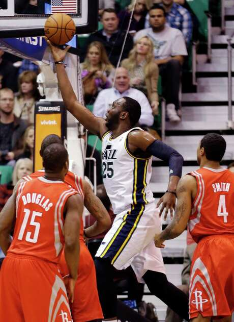 Toney Douglas (15) and the Rockets look every bit like the NBA's No. 27 scoring defense on this drive by the Jazz's Al Jefferson (25). Photo: Rick Bowmer, STF / AP