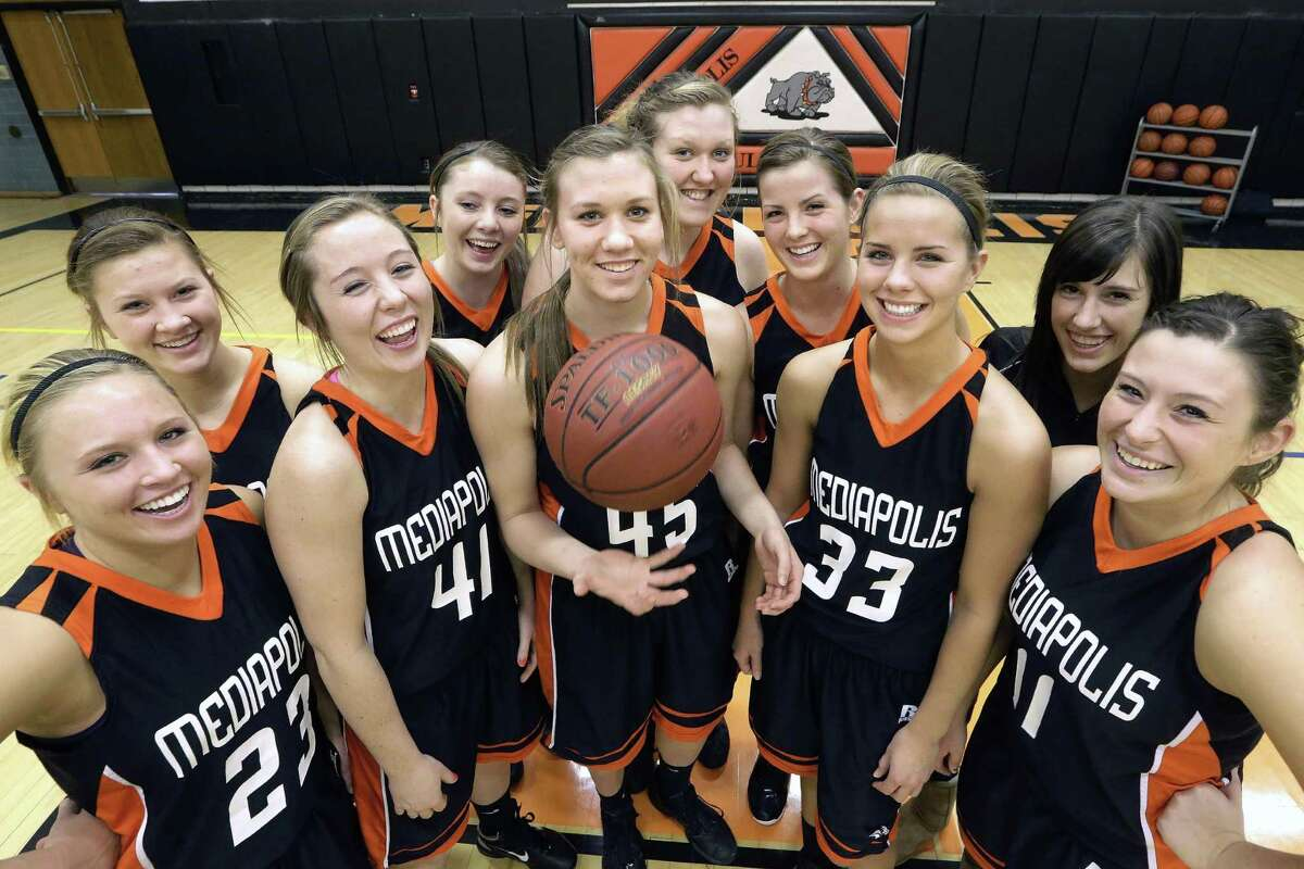 In this Feb. 1, 2013 photo, members of the Mediapolis High School Girls Basketball team pose for a photo in Mediapolis, Iowa. The dynamic of one of Iowa's best high school basketball teams is defined by an extraordinary coincidence of five sets of sisters. Front row: Allison Hedges, Darby Massner, Heidi Hillyard, Rachel Holsteen, Aubrey Siegle. Back row: Ashley Hedges, Allie Massner, Haley Hillyard, Jessica Holsteen, Chloe Siegle. (AP Photo/Seth Perlman)