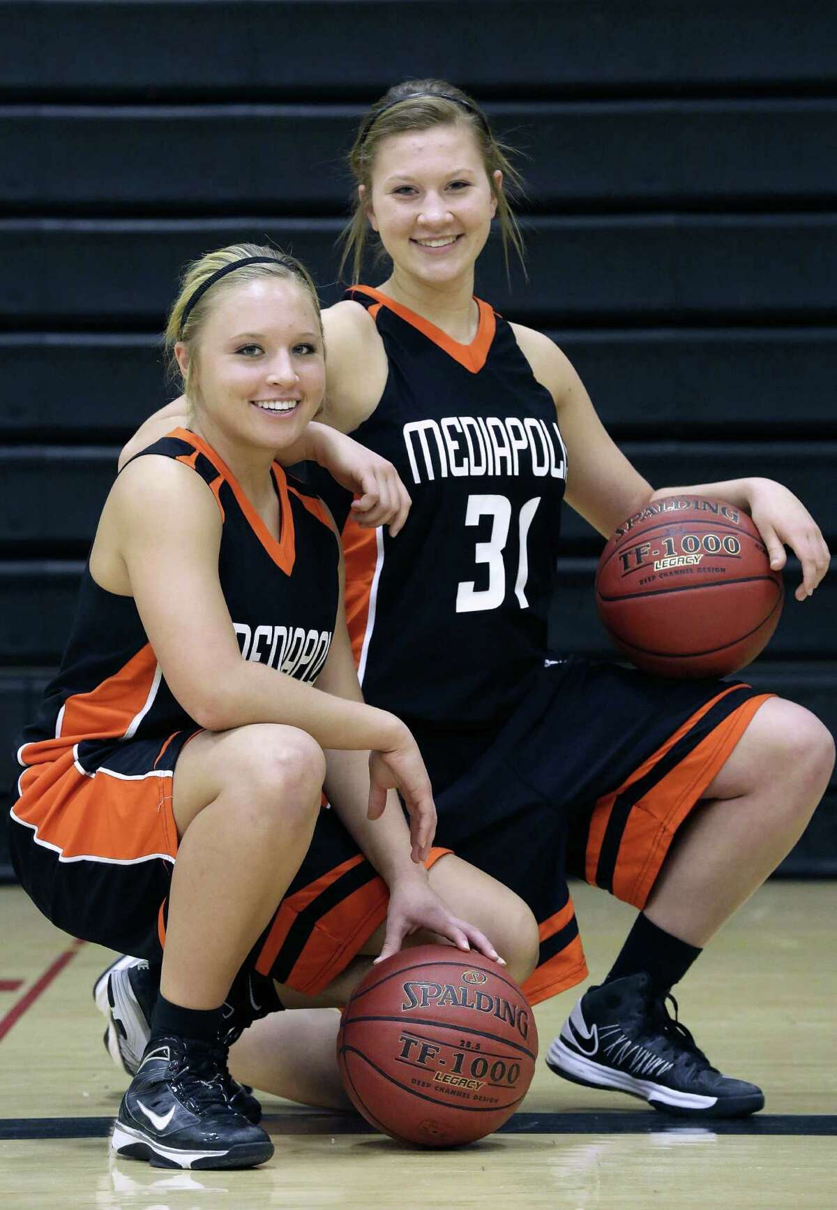 In this Feb. 1, 2013 photo, Mediapolis High School Girls Basketball team players Allison Hedges, left, and her sister Ashley Hedges, right, pose for a photo in Mediapolis, Iowa. The dynamic of one of Iowa's best high school basketball teams is defined by an extraordinary coincidence of five sets of sisters. (AP Photo/Seth Perlman)