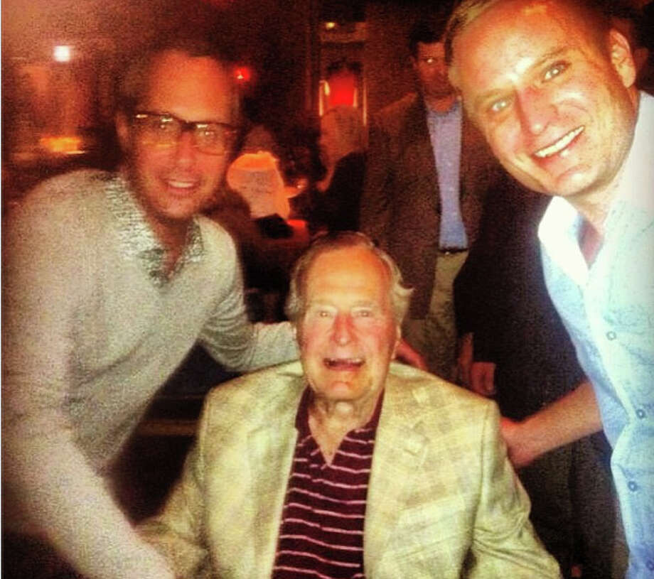 George H.W. Bush is flanked by well-wishers Mark Sullivan, left, and Jason Reeves, right, at Gigi's Asian Bistro & Dumpling Bar on Saturday night. (Posted by Janet Shamlian on Instagram)