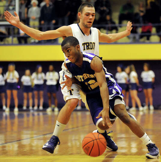 CBA's Tyrell Ramsey (12), center, drives past Troy's Imre Megyeri (22), left, and Dyaire Holt (11) d