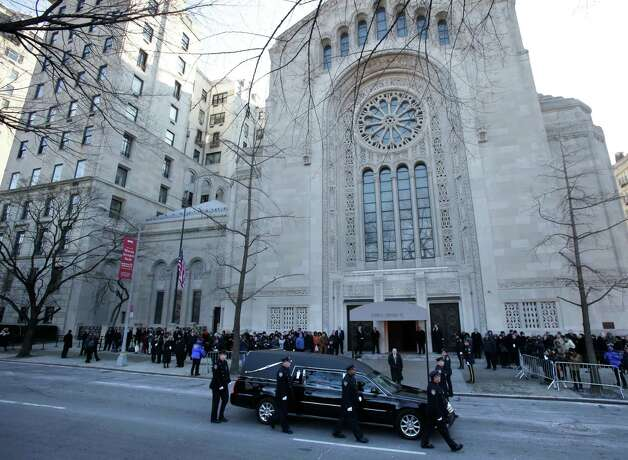 Police walk with the hearse containing the body of former New York City Mayor Ed Koch as it arrives at Temple Emanu-El for his funeral in New York, Monday, Feb. 4, 2013.   Koch died Friday of congestive heart failure at age 88.  (AP Photo/Seth Wenig) Photo: Seth Wenig