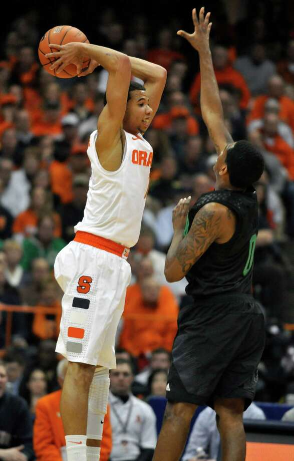 Syracuse's Michael Carter-Williams passes over Notre Dame's Eric Atkins during the first half of an NCAA college basketball game in Syracuse, N.Y., Monday, Feb. 4, 2013. (AP Photo/Kevin Rivoli) Photo: KEVIN RIVOLI