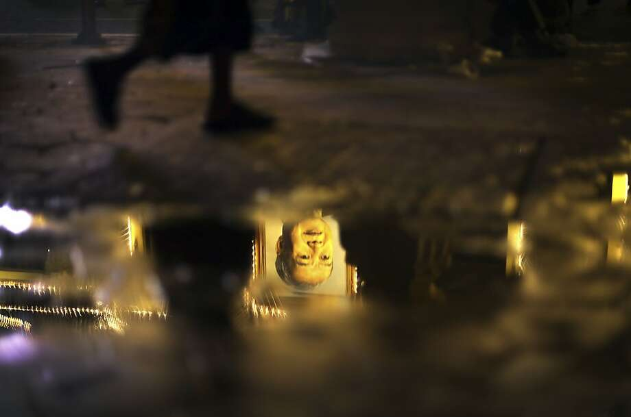 "A young boy walks pass a puddle with a reflection of a portrait of the late former Cambodian King Norodom Sihanouk in Phnom Penh, Monday, Feb. 4, 2013. Hundreds of thousands of mourners gathered in Cambodia's capital Monday for the cremation of former King Norodom Sihanouk, the revered ""King-Father,"" who survived wars and the murderous Khmer Rouge regime to hold center stage in the Southeast Asian nation for more than half a century. Photo: Wong Maye-E, Associated Press"