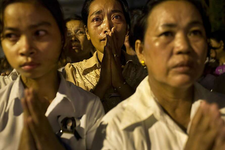 Cambodian mourners cry and pray outside a crematorium as the late King Norodom Sihanouk is cremated