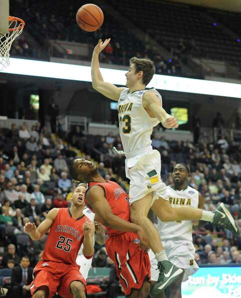 Siena's Rob Poole is fouled by Fairfield's Derek Needham during a basketball game at the Times Union