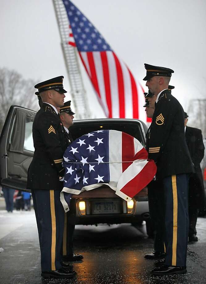 An honor guard carries the casket of Staff Sgt. Mark Schoonhoven into Winkel Funeral Home in Otsego, Mich., on Monday, Feb. 4, 2013. Schoonhoven, a Plainwell native, died Jan. 20 from injuries sustained from an IED attack in Afghanistan. Photo: Mark Bugnaski, Associated Press