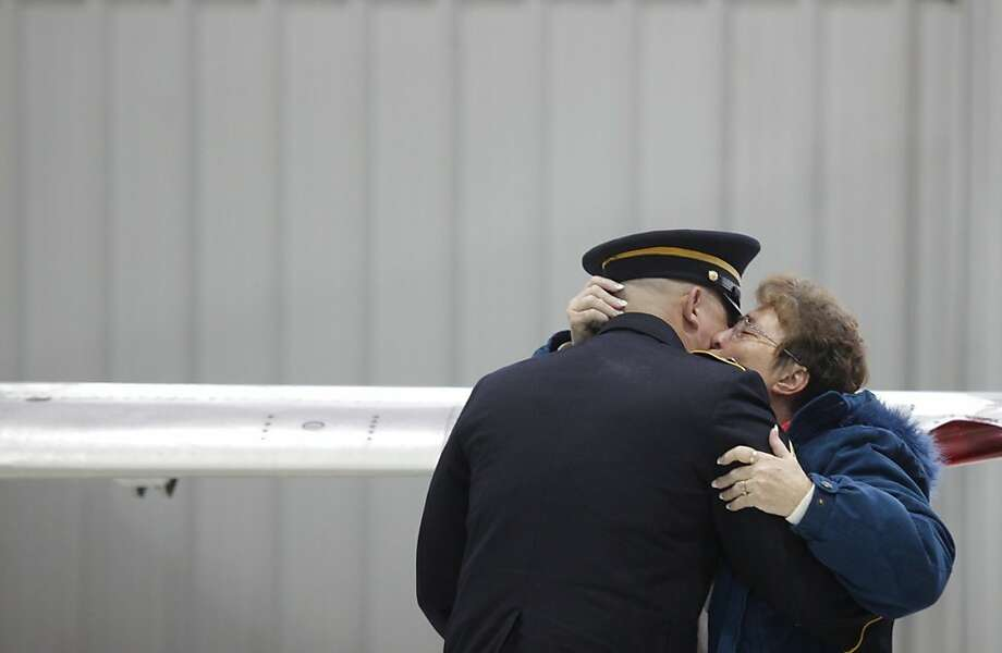 Deb Schoonhoven kisses Brian Gott, as family and friends gather at Duncan Aviation in Kalamazoo, Mich., to bring Staff Sgt. Mark Schoonhoven to Otsego, Mich., Monday, Feb. 4, 2013. Schoonhoven, a Plainwell native, died Jan. 20 from injuries sustained from an IED attack in Afghanistan. Photo: Mark Bugnaski, Associated Press