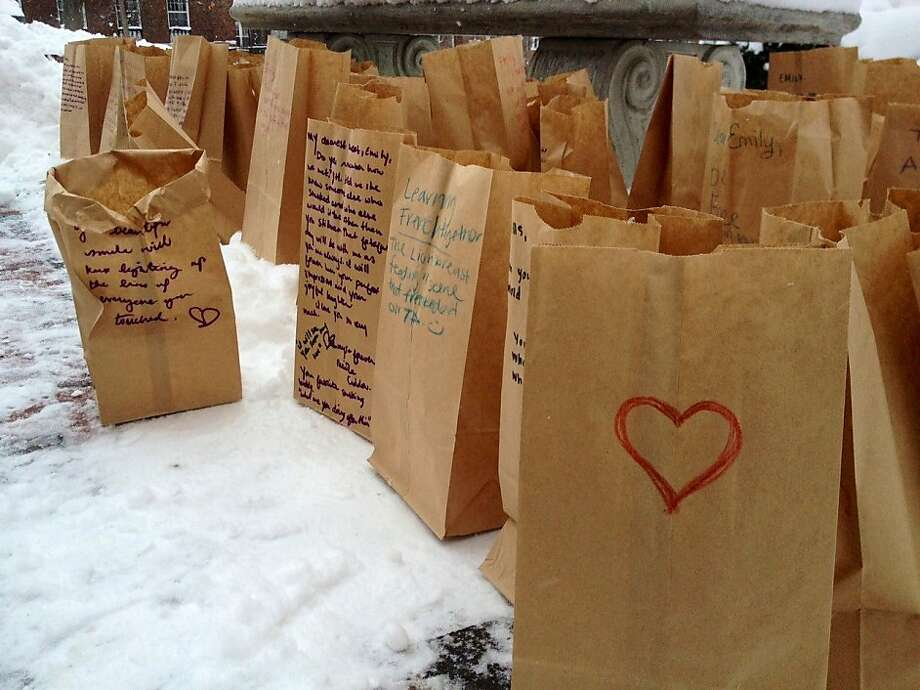 In this photo taken Sunday, Feb. 3, 2013 notes written by mourners at a memorial service for Emily Stillman, 19, a sophomore at Kalamazoo College, to and memories of Stillman are placed in paper bags that served as lanterns in Kalamazoo, Mich. They placed tealights in the bags and placed them around a bench outside the chapel. More than 60 paper lanterns surrounded the bench by the end of the memorial service. Stillman had died Feb. 3 due to complications from bacterial meningitis. Photo: Emily Monacelli, Associated Press