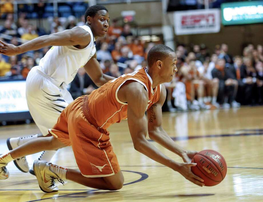 Demarcus Holland, right, makes a pass to save the possession for Texas while being defended by Juwan Staten. Photo: DAVID SMITH, FRE / FR93543 AP