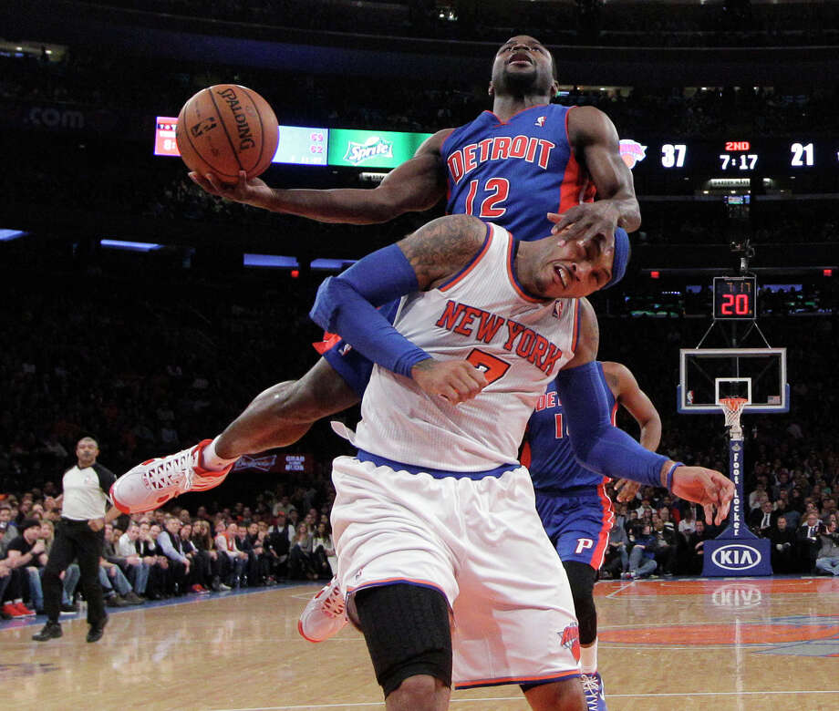 Detroit's Will Bynum (12) uses Carmelo Anthony (7) to stabilize himself as he goes up for a shot during Monday's game at New York. The Knicks won 99-85. Photo: Kathy Willens, STF / AP