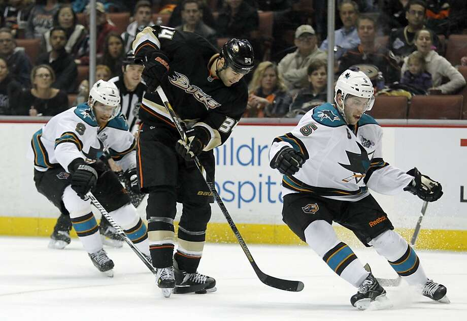 Anaheim Ducks center Daniel Winnik, center, controls the puck as San Jose Sharks left wing Martin Havlat, left, of the Czech Republic, and Sharks defenseman Jason Demers (5) defend during the second period of their NHL hockey game, Monday, Feb. 4, 2013, in Anaheim, Calif. (AP Photo/Alex Gallardo) Photo: Alex Gallardo, Associated Press