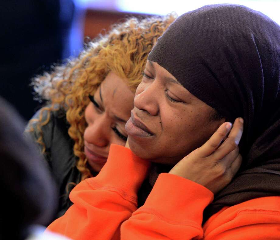 Roshana McArthur, right, the mother of the stabbing victim Takim Smith is comforted by her relative Charmine Chaney, left, Tuesday morning, Feb. 5, 2013, in Troy City Court in Troy, N.Y. during the arraignment of the defendants, Ahziarh Carter, 16, and Keith Ferguson, 17. They are charged with 2nd degree murder.    (Skip Dickstein/Times Union) Photo: SKIP DICKSTEIN