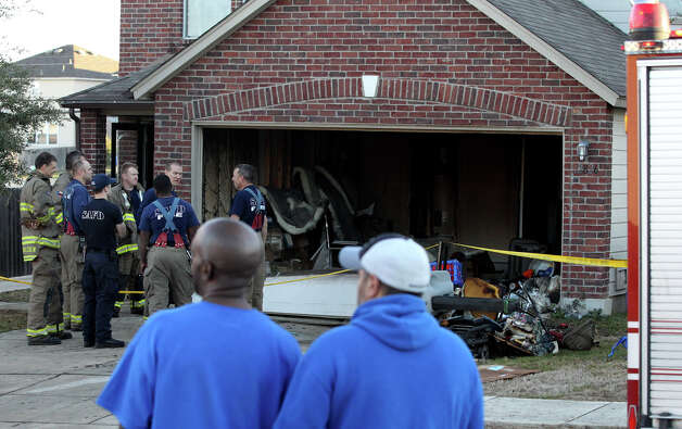 San Antonio firefighters gather while arson investigates the cause of a house fire that broke out shortly before 7:00 a.m. Tuesday February 5, 2013 on the 12,800 block of Falcons Nest. Fire Captain Chuck Anz said there was heavy smoke coming out of the garage when fire trucks arrived and that there was about $5,000 in damages. There were no injuries during the incident. Photo: JOHN DAVENPORT, San Antonio Express-News / ©San Antonio Express-News/Photo Can Be Sold to the Public