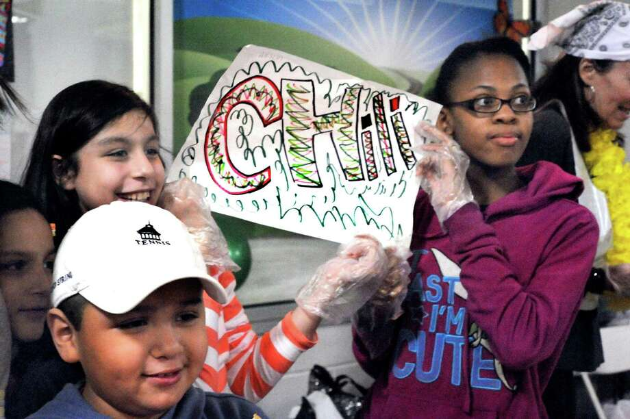 Members of Danbury Grass Roots Tennis, including Jason Marroquin, 7, Emily Rojas, 9, left center, and Natasha Wright, 12, right, advertised their chili at the annual Chili Winter Warm-Up in the Danbury Ice Arena Sunday, Feb.19, 2012. This year's event will be held Sunday, February 10. Photo: Michael Duffy