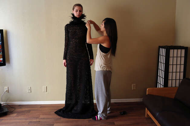 Designer Samantha Plasencia, right, adjusts her design worn by Texas State student and model Haley Cook as Plasencia photographs Cook in all of her designs she'll be showing at Mercedes-Benz Fashion Week in New York for model cards for the show's lineup, at her home in San Antonio on Thursday, Jan. 31, 2013. Photo: Lisa Krantz, San Antonio Express-News / © 2012 San Antonio Express-News
