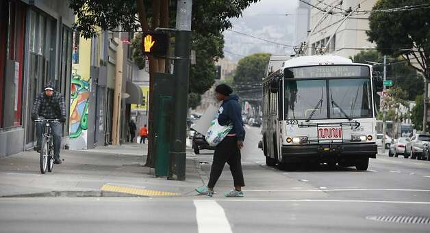 A 14 Mission line Muni bus heads east bound on Mission Street as a bicyclist moves alongside it on the sidewalk on Monday, February 4, 2013 in San Francisco, Calif. Photo: Lea Suzuki, The Chronicle