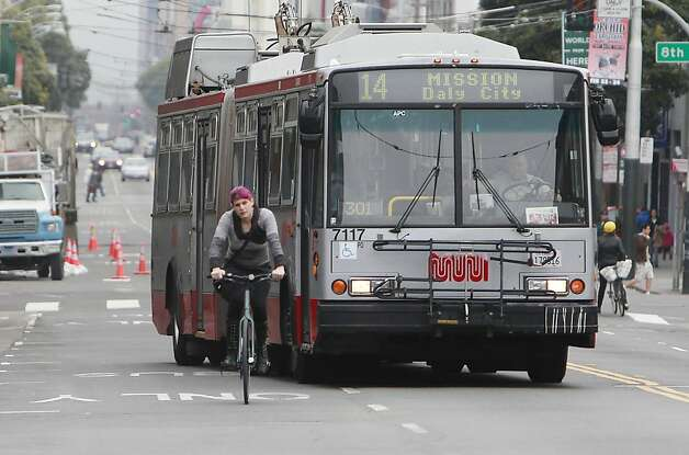 Naomi Seyfer of Berkeley on a bicycle and a 14 Mission line Muni bus make their way west bound on  Mission Street on Monday, February 4, 2013 in San Francisco, Calif. Photo: Lea Suzuki, The Chronicle