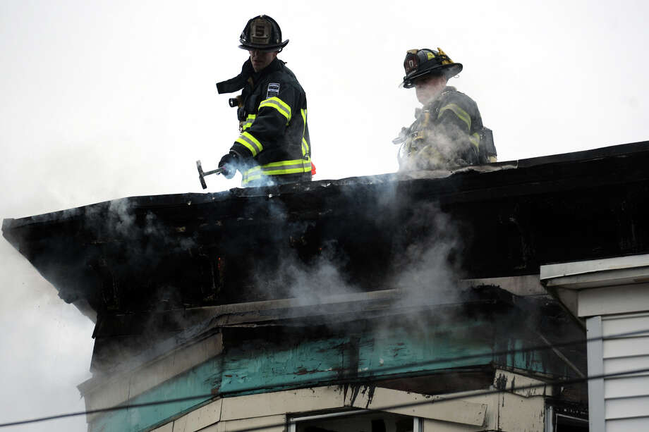 Bridgeport firefighters work on a fire at a three-story house, 69 Ives Court in Bridgeport, Conn., Feb. 5th, 2013. Photo: Ned Gerard / Connecticut Post